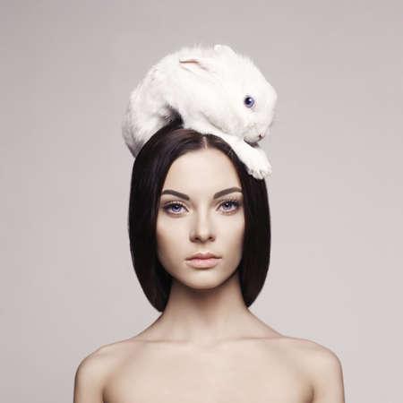 conejo: Retrato de la moda de estudio de hermosa dama con conejo blanco