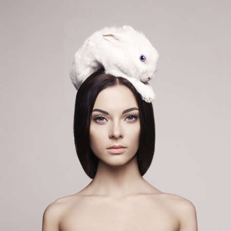 rabbit: Studio fashion portrait of beautiful lady with white rabbit Stock Photo