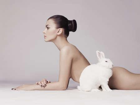 mujeres jovenes desnudas: Foto de la manera del estudio de la mujer elegante desnuda con conejo blanco