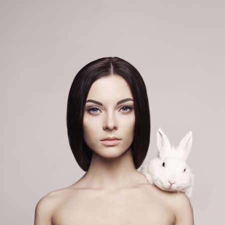 брюнетка: Студия моды портрет красивой женщины с белым кроликом