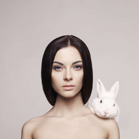 bunny rabbit: Studio fashion portrait of beautiful lady with white rabbit Stock Photo