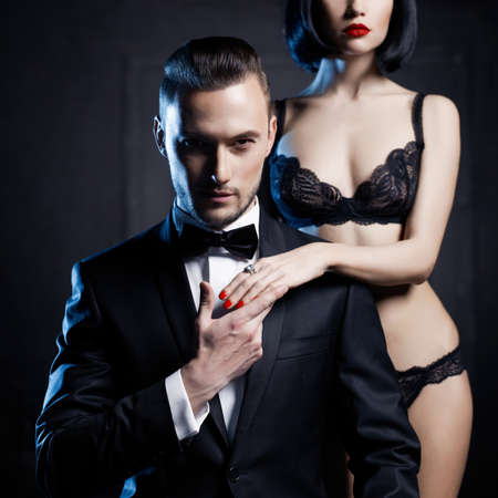 naked young people: Fashion studio photo of a sensual couple in lingerie and a tuxedo