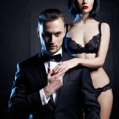 pareja desnuda: Moda foto de estudio de una pareja sensual en ropa interior y un esmoquin
