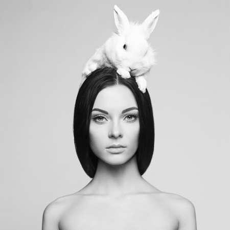 Studio fashion portrait of beautiful lady with white rabbit Foto de archivo