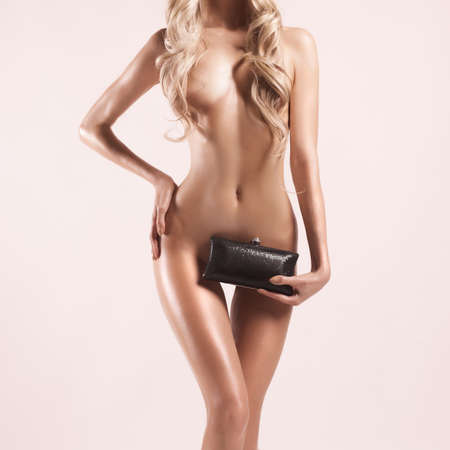 nude: Fashion studio photo of elegant nude woman with clutch Stock Photo