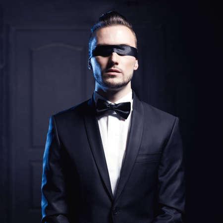 desnudo masculino: Retrato de hombre con estilo en un elegante traje negro con los ojos vendados