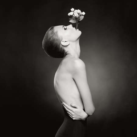 Fashion art photo of elegant naked lady with flowers in her mouth Stock Photo