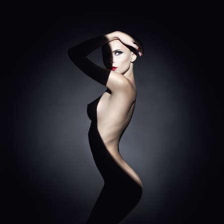 Fashion art studio portrait of elegant naked lady with shadow on her body