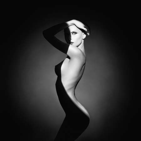 Fashion art studio portrait of elegant naked lady with shadow on her body