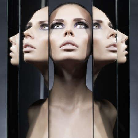 검은 배경에 여자와 거울의 패션 스튜디오 초상화