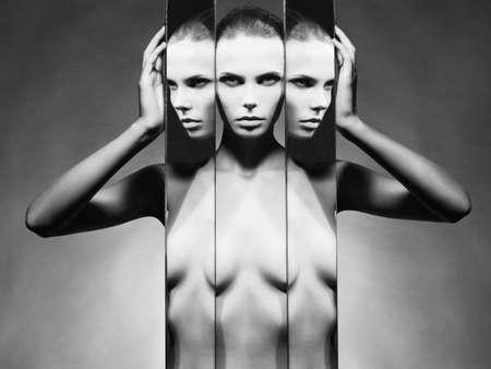 femme noire nue: Portrait en studio de mode de femme �l�gante nu et miroirs sur fond noir Banque d'images