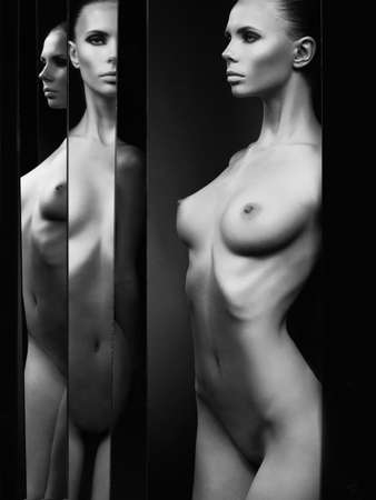 nude model: Fashion studio portrait of nude elegant woman and mirrors on black background Stock Photo