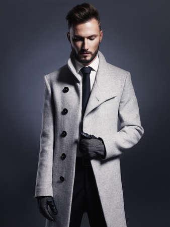 エレガントな秋のコートでハンサムなスタイリッシュな男の肖像
