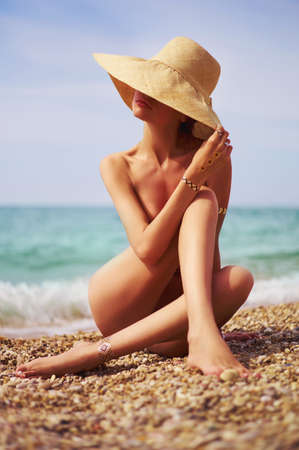 hat nude: Elegant naked lady at the sea. Summer travel photos Stock Photo