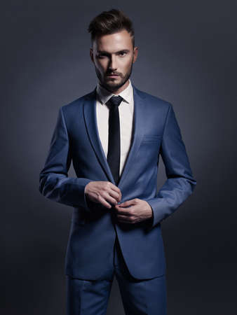 model posing: Portrait of handsome stylish man in elegant blue suit