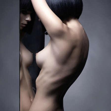 woman naked body: Fashion studio portrait of nude elegant woman and mirrors on black background Stock Photo