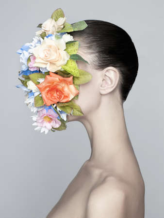 nude girl young: Concept fashion studio portrait of nude elegant lady with flower on her face