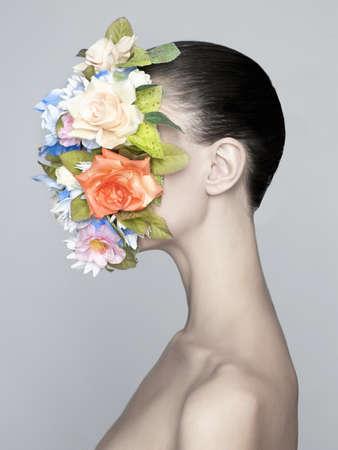 nudo integrale: Concetto di moda ritratto in studio di nudo signora elegante con il fiore sulla sua faccia