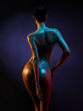 modelo desnuda: Foto del arte de la moda del modelo desnudo elegante en los focos de colores claros