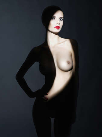 erotic woman: Fashion art studio portrait of elegant naked lady with shadow on her body