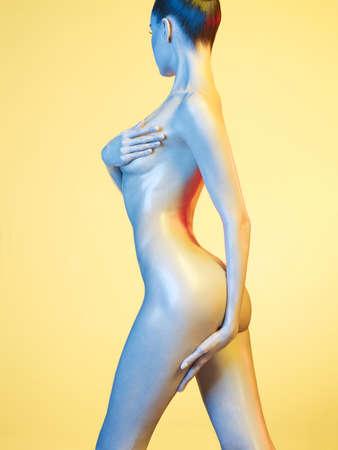 desnudo artistico: Foto del arte de la manera del modelo elegante desnuda en los focos de colores claros Foto de archivo