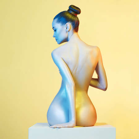 nude body: Fashion art photo of elegant nude model in the light colored spotlights