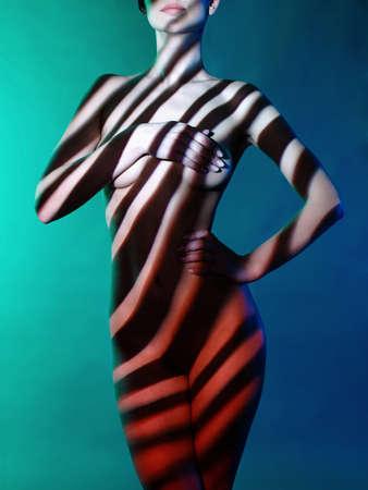 Fashion art studio foto van elegante naakte dame met schaduwen op haar lichaam Stockfoto