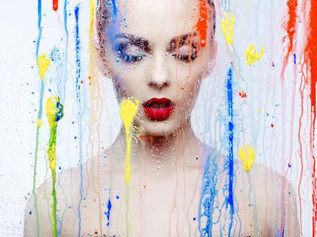 fashion art: Fashion art studio photo of beautiful model through the glass with bright colors