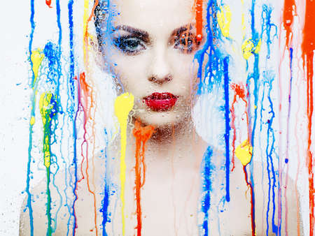 female model: Fashion art studio photo of beautiful model through the glass with bright colors