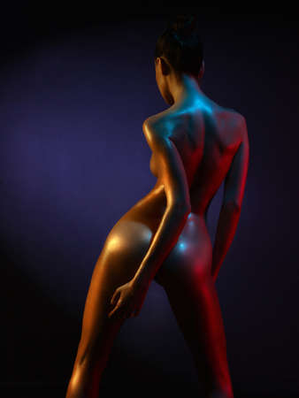 sex pose: fashion art photo of sexy nude stripper in the night-club. Perfect female body  with oil skin