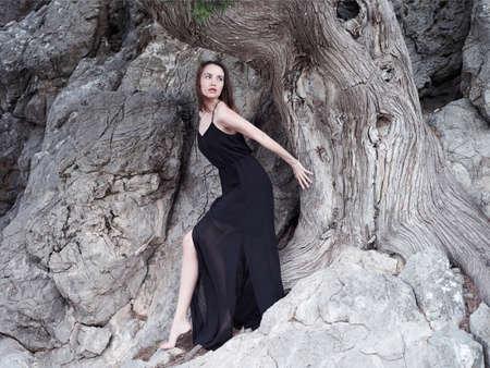 Ambientazione esterna moda foto di giovane e bella donna al antico albero possente