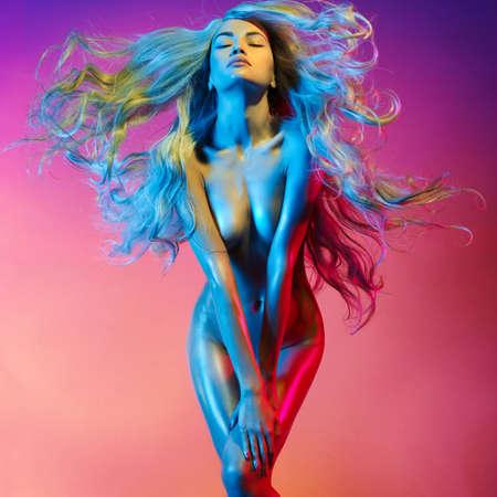 Nude schöne Blondine tanzen in bunten Licht. Erotisches Portrait der reizvollen Frau mit den langen Haaren. Standard-Bild - 62176617