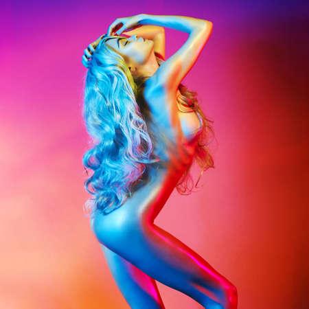 Bella bionda nuda danza nella luce colorata. Ritratto erotico di donna sexy con i capelli lunghi.