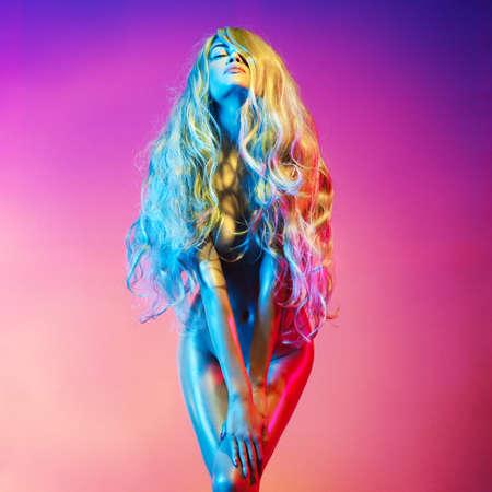 カラフルなライトで踊る裸の美しいブロンド。長い毛でセクシーな女性の官能的な肖像画。