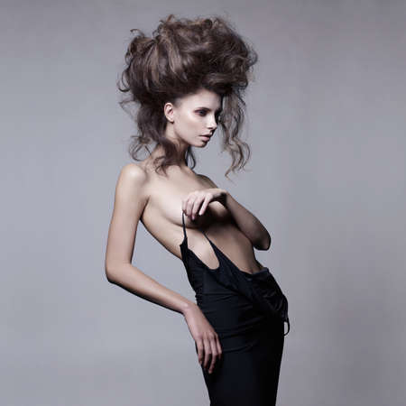 to undress: Studio fashion portrait of beautiful sensual woman with volume wavy hair. Big hair