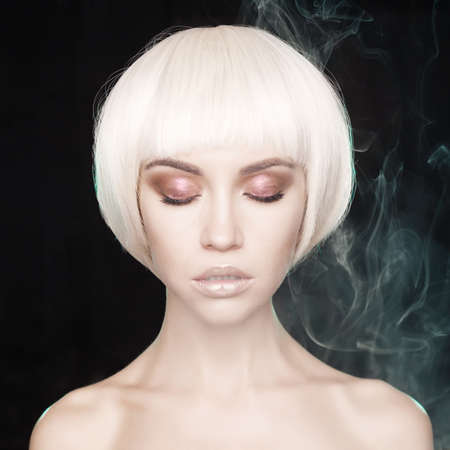 Art fashion studio portrait of beautiful blonde with short haircut. Glamour photo with smoke on background