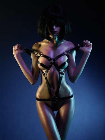 sexy young woman in erotic fetish wear dancing striptease in nightclub. Beautiful nude body of sensuality elegant lady. Stock Photo