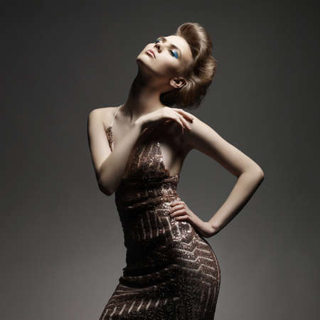 sexy girl dance: Studio fashion photo of elegant beautiful lady in gold dress. Young sexy woman with art modern haircut.