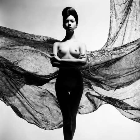 Black and white art fashion studio photo of nude elegant woman surrounded by flowing draperies. Perfect body. Beauty and health