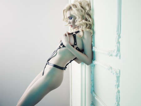 Fashion photo of nude elegant woman in provocative leather swordbelt in classical interior. Fetish lingerie