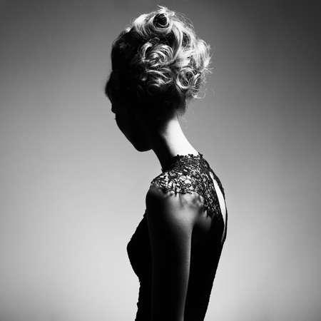 Zwart-wit portret van mooie slanke vrouw met elegant kapsel op grijze achtergrond Stockfoto