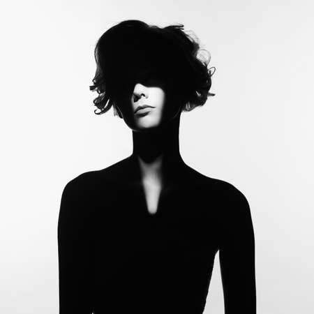 黒と白の芸術は美しい女性の彼女の顔に光のビームとシュールなポートレートをファッション