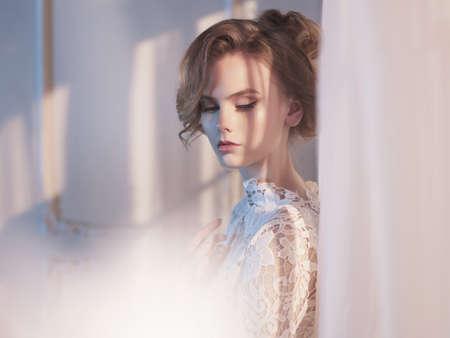 Kunst mode foto van mooie prachtige vrouw in kant jurk bij het raam. Schoonheid en gezondheid. Trouw stijl. Bruidsmorgen