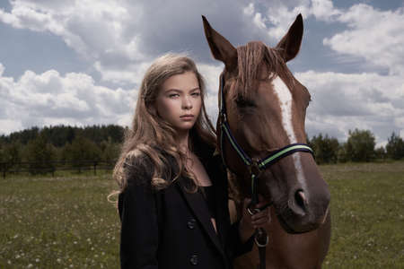 Outdoor art fashion photo of beautiful young lady with horse. Lizenzfreie Bilder