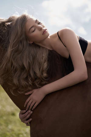 Outdoor art fashion photo of beautiful young lady with horse. photo