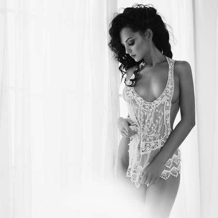 窓にランジェリーで美しいゴージャスな女性のアートブドワールファッション写真。完璧なボディ。美容と健康