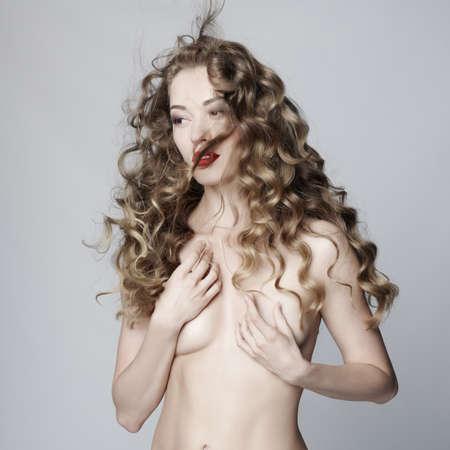Studio fashion art portrait of beautiful sensual woman with elegant hairstyle on gray background
