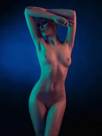 Studiomodekunstfoto des eleganten Aktmodells in den hellen farbigen Scheinwerfern