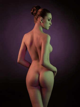 Studio fashion art photo of elegant nude model in the light colored spotlights