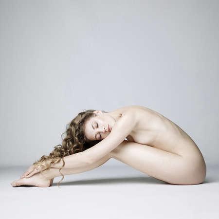 nackte sexy schöne Frau mit langer stilvoller Frisur werfen auf weißem Hintergrund im photostudio auf. Erotisches Portrait der eleganten nackten Dame mit vollkommenem nacktem Körper. Sexuelle Fotografie der jungen nackten Blondine. Sinnliches Modell mit langem Haar sitzt im Studio. Hübscher Streifen